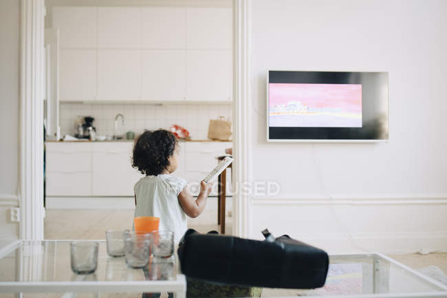 Rear view of girl with remote control watching TV at home — Photo de stock