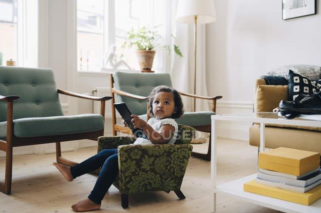 Полная длина девушки, держащей цифровой планшет, сидя на маленьком кресле дома — стоковое фото