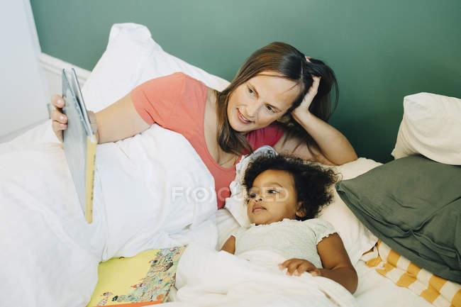 Усміхнена мати показуючи картину книгу дочки під час сну на ліжку вдома — стокове фото