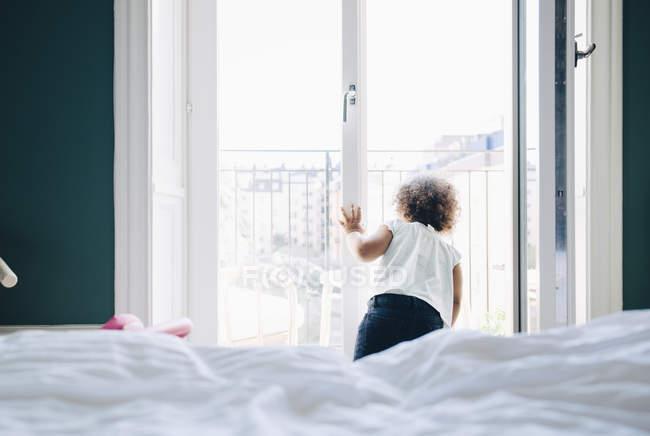 Menina bonito que olha através do indicador ao estar no quarto em casa — Fotografia de Stock