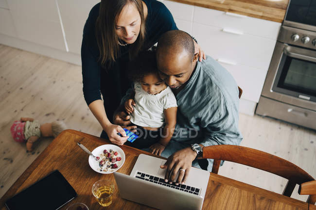 High angle view of parents with daughter shopping online on laptop at dining room — Fotografia de Stock