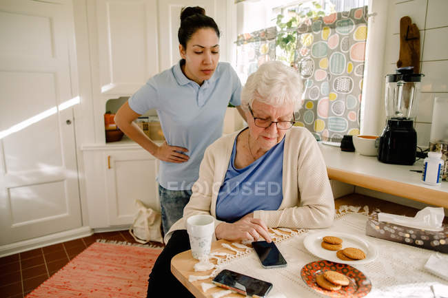 Young female volunteer looking at retired elderly woman using smart phone in nursing home — Stock Photo