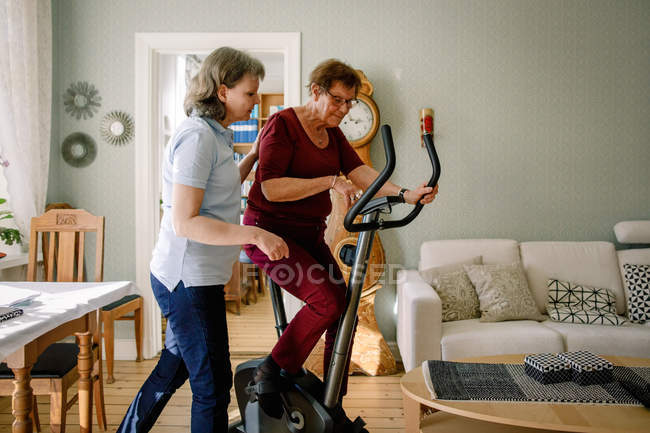 Mature female physical therapist assisting elderly woman on exercise bike at nursing home — Stock Photo
