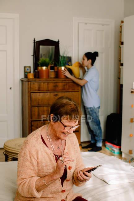 Улыбающаяся пожилая женщина в отставке, пользующаяся смартфоном, пока волонтёр поливает растения в спальне в доме престарелых — стоковое фото