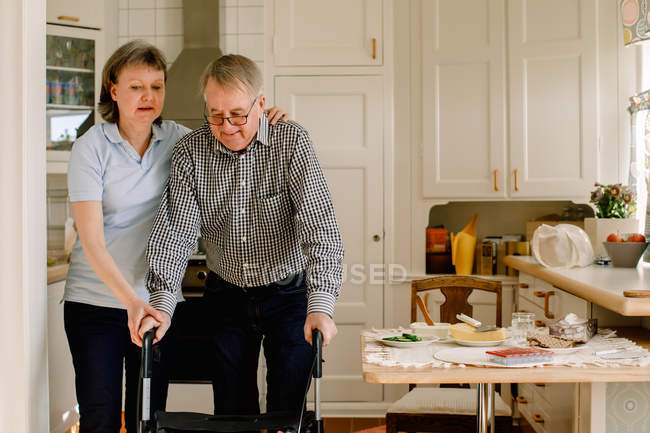 Mature female caregiver assisting retired man walking with rollator in kitchen at nursing home — Stock Photo