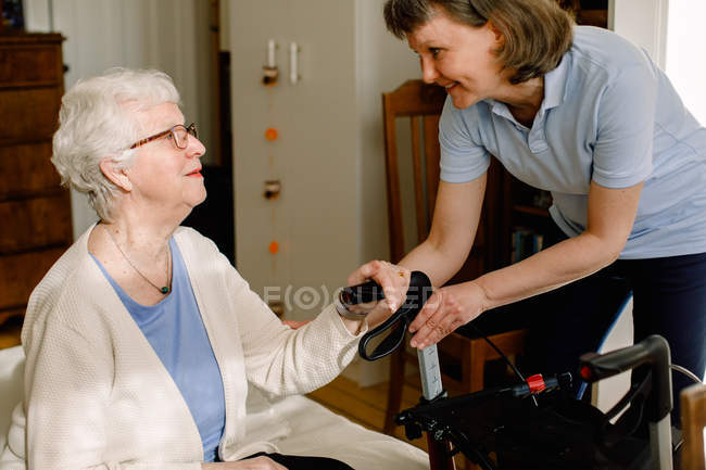 Smiling female healthcare worker looking at senior woman sitting with rollator in bedroom at nursing home — Stock Photo