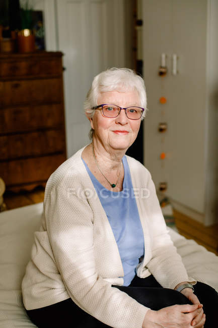 Portrait of smiling retired senior woman sitting on bed in nursing home — Stock Photo