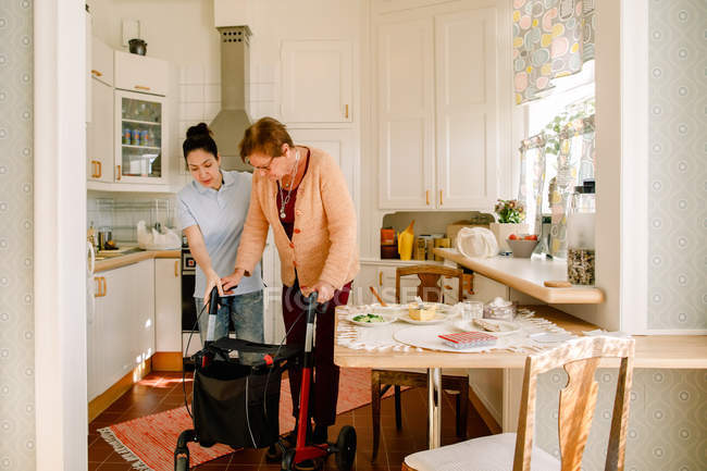 Young female volunteer assisting retired elderly woman with rollator in kitchen at nursing home — Stock Photo