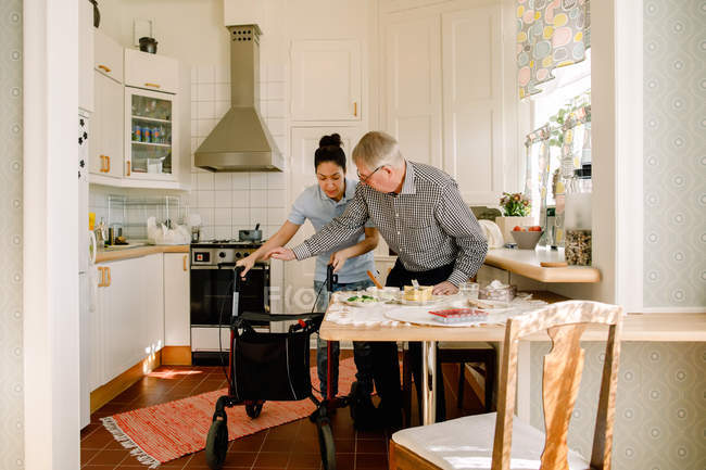 Young female volunteer assisting retired elderly man with rollator in kitchen at nursing home — Stock Photo