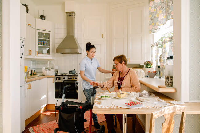 Young female volunteer assisting retired senior woman in getting up at nursing home — Stock Photo