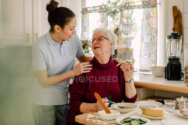 Retired senior woman eating breakfast while talking with female volunteer at nursing home — Stock Photo