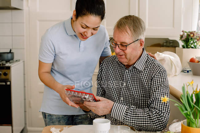 Smiling young female social worker explaining medicines to retired senior man in nursing home — Stock Photo