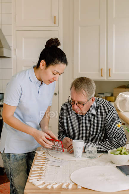 Young female healthcare worker explaining medicines to retired elderly man sitting at table in nursing home — Stock Photo