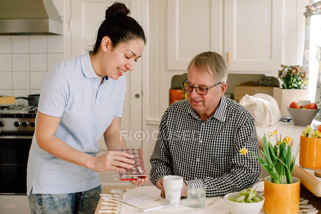 Smiling young female healthcare worker explaining medicines to retired elderly man sitting at table in nursing home — Stock Photo