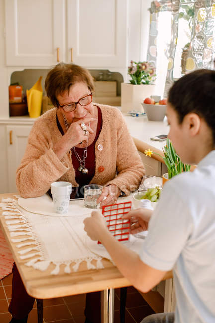 Young female healthcare worker discussing over medicines with senior woman at table in nursing home — Stock Photo