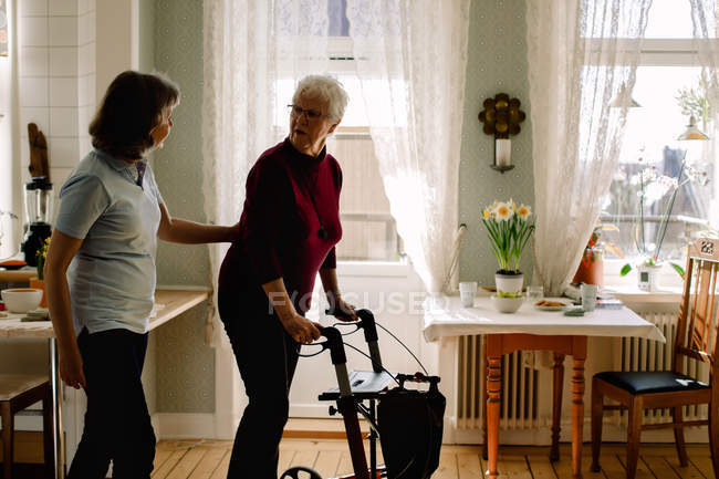 Side view of female healthcare worker supporting elderly woman with rollator in nursing home — Stock Photo