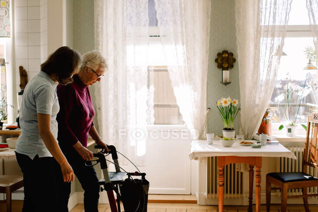 Side view of female healthcare worker assisting elderly woman with rollator in nursing home — Stock Photo