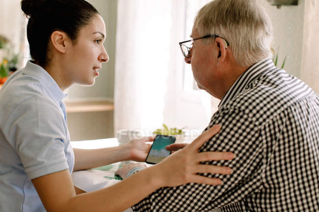 Young female social worker assisting retired man with smart phone in nursing home — Stock Photo