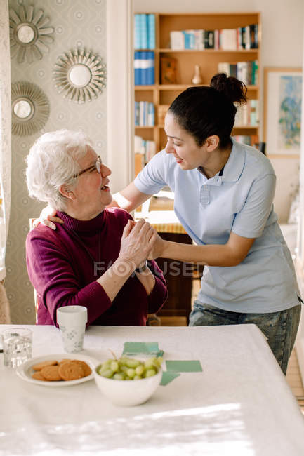 Smiling retired senior woman holding hands of young female volunteer while talking in nursing home — Stock Photo