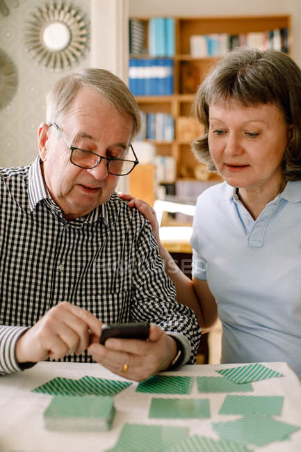 Mature female social worker assisting retired senior man in using smart phone at table in nursing home — Stock Photo