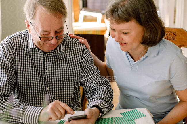 Smiling mature female social worker looking at retired senior man using smart phone in nursing home — Stock Photo