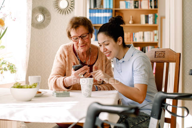 Smiling young female social service worker assisting retired elderly woman using smart phone at table in nursing home — Stock Photo