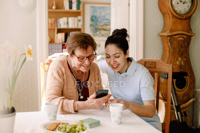 Smiling young female volunteer assisting retired elderly woman using smart phone at table in nursing home — Stock Photo