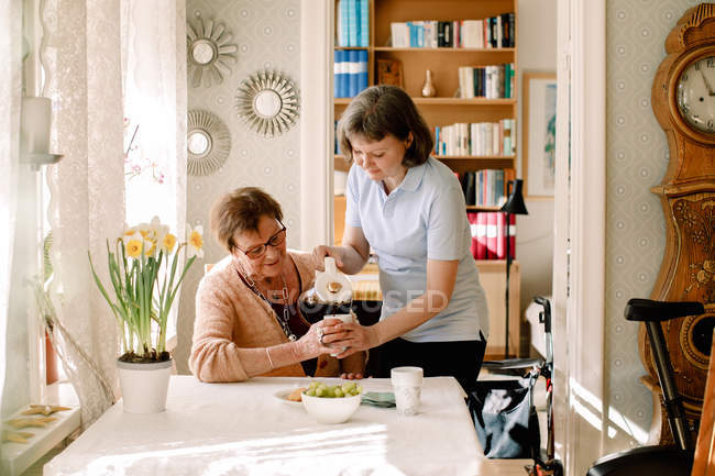 Female healthcare worker is pouring coffee for retired senior woman at table in nursing home — Stock Photo
