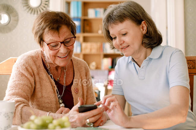 Smiling healthcare worker is assisting elderly woman in using smart phone at nursing home. — Stock Photo