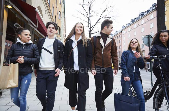 Amis adolescents souriants, hommes et femmes, marchant sur les sentiers de la ville — Photo de stock