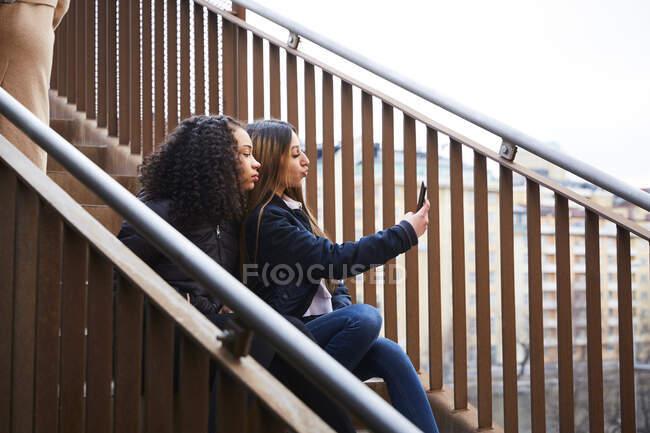 Adolescente menina tomando selfie com a amiga enquanto se senta na escadaria — Fotografia de Stock