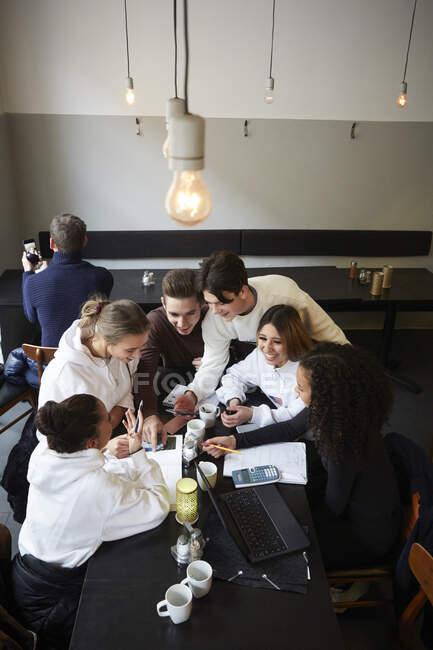 Heureux mâle et femelle adolescent amis à table dans café — Photo de stock