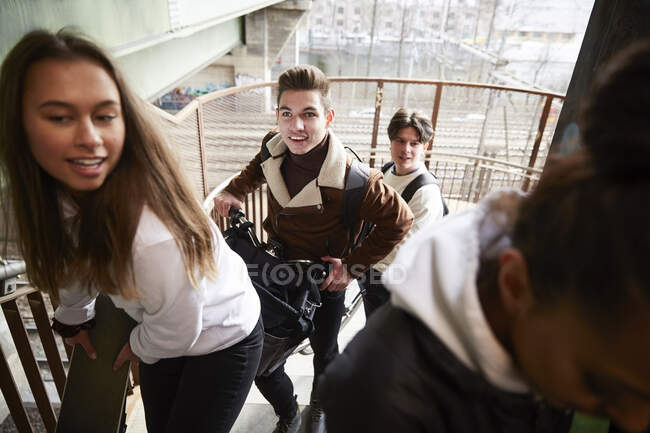 Male and female teenage friends carrying bicycle and electric push scooter on staircase — Stock Photo