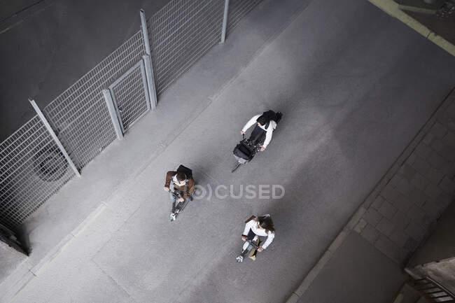 Vue grand angle des amis masculins et féminins chevauchant scooters électriques push et vélo sur la rue en ville — Photo de stock
