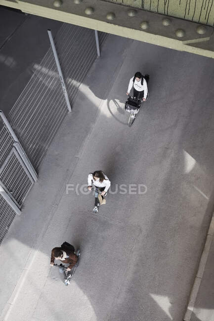 High angle view of male and female teenage friends riding electric push scooters and bicycle on road in city — Stock Photo
