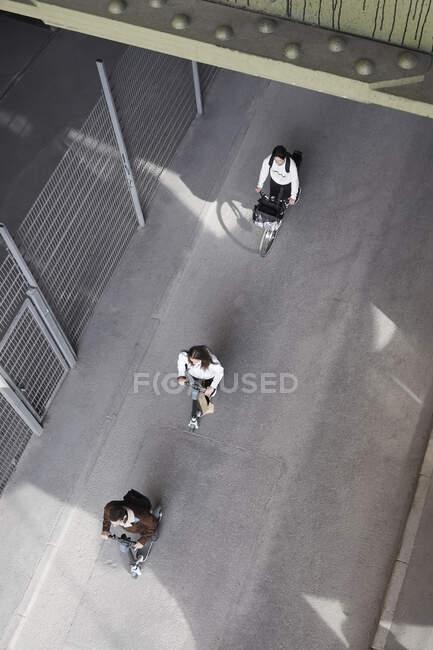 Vue grand angle des hommes et des femmes adolescents amis équitation scooters électriques push et vélo sur la route en ville — Photo de stock