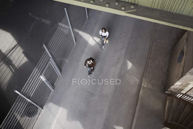 Alta visão angular de amigos do sexo masculino e feminino montando scooters empurrão elétrico na rua na cidade — Fotografia de Stock