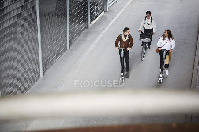 Vista ad alto angolo di amici adolescenti che guidano scooter elettrici a spinta e bicicletta su strada in città — Foto stock