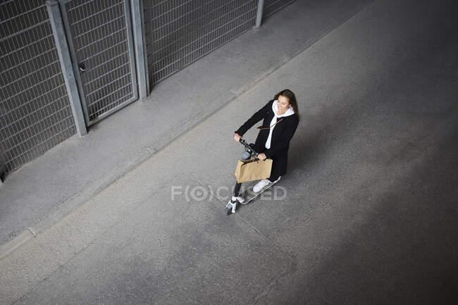 Vue grand angle de l'adolescente chevauchant scooter électrique push sur la rue en ville — Photo de stock