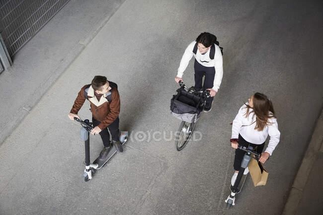 Alta visão angular de amigos do sexo masculino e feminino montando scooters empurrão elétrico e bicicleta na estrada na cidade — Fotografia de Stock