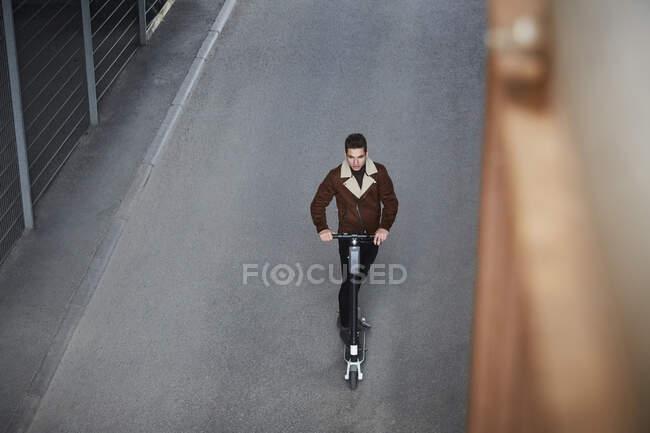 Vue grand angle de adolescent garçon équitation électrique pousser scooter sur la rue en ville — Photo de stock