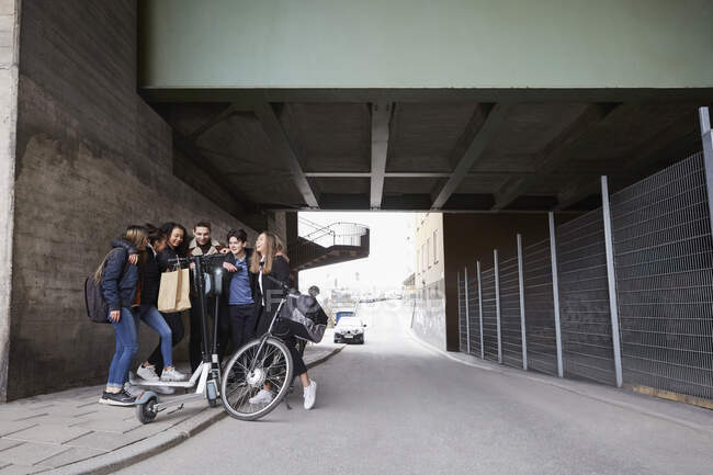 Teenage male and female friends with push scooters and bicycle on sidewalk below bridge — Stock Photo