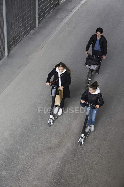 Alta visão angular de amigos do sexo masculino e feminino montando scooters empurrão elétrico e bicicleta na rua na cidade — Fotografia de Stock