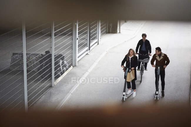 Vista ad alto angolo di amici adolescenti maschi e femmine in sella a scooter elettrici a spinta e bicicletta in strada in città — Foto stock