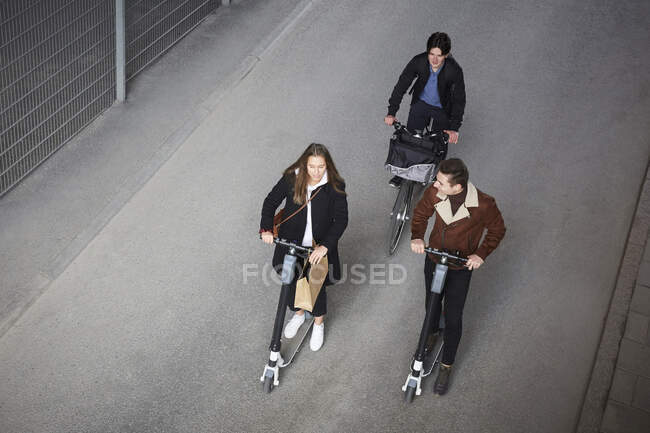 High angle view of teenage friends riding electric push scooters and bicycle on street in city — Stock Photo