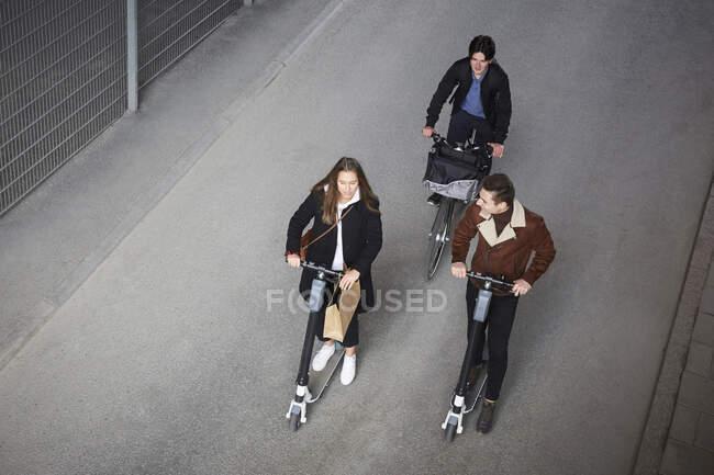 Vista ad alto angolo di amici adolescenti che guidano scooter elettrici a spinta e bicicletta in strada in città — Foto stock