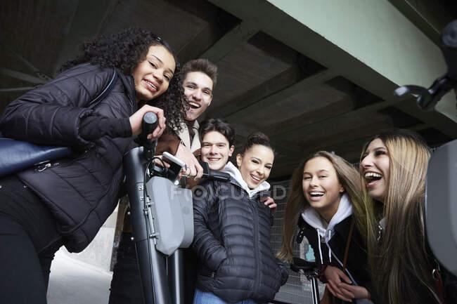 Niederwinkelporträt glücklicher männlicher und weiblicher Teenager-Freunde mit elektrischen Schieberollern unter der Brücke — Stockfoto
