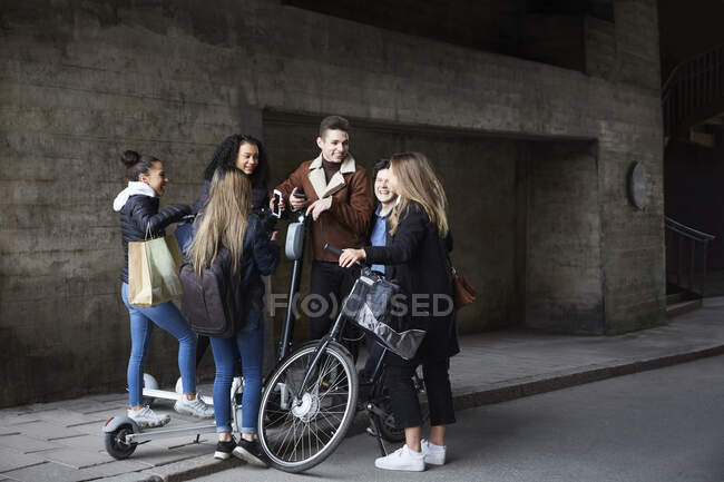 Smiling teenage male and female friends with push scooters and bicycle on footpath — Stock Photo