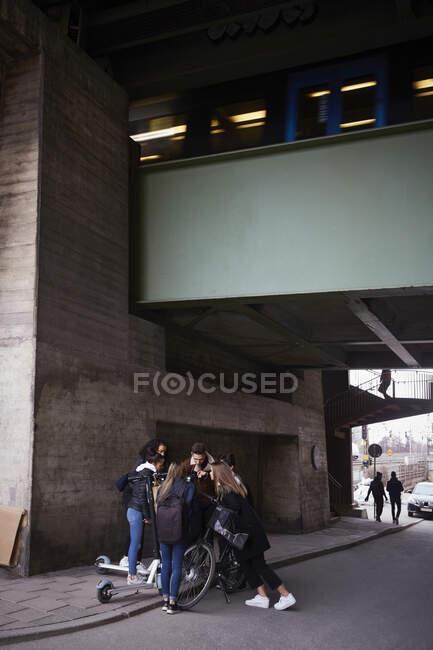 Teenager mit Roller und Fahrrad auf Fußweg unter Brücke — Stockfoto