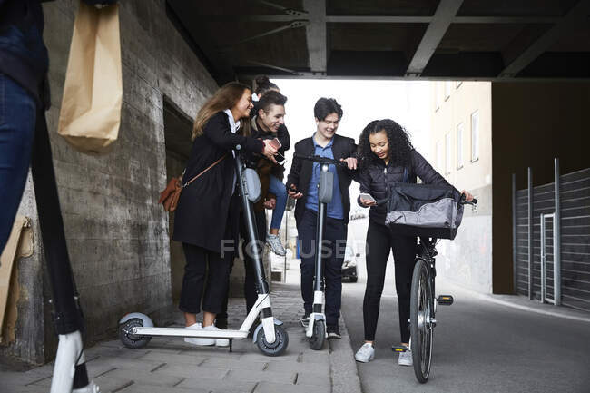 Felices amigos adolescentes masculinos y femeninos con scooters eléctricos mirando el teléfono móvil debajo del puente - foto de stock